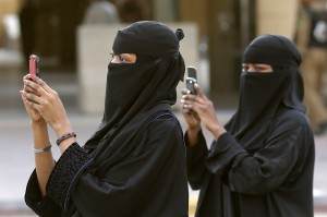 Women use their mobilephones to take pictures outside the Imam Turki bin Abdullah mosque as residents perform Eid al-Fitr morning prayers to mark the end of the holy fasting month of Ramadan Sunday, Aug. 19, 2012, in Riyadh. (AP Photo/Hassan Ammar)